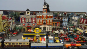a lego building set up with various lego cars and lego trains